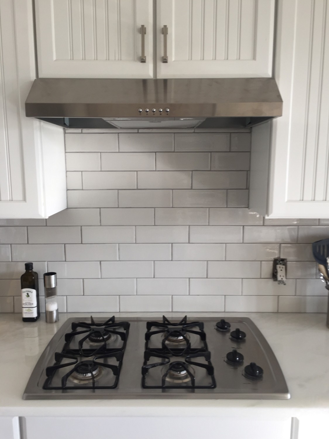 The kitchen has been completely renovated with fresh white cabinets - The Gigantic Oversized Over The Range Microwave Has Been Replaced With This Sleek Stainless Steel Vent Hood And A Classic White Subway Tile Backsplash